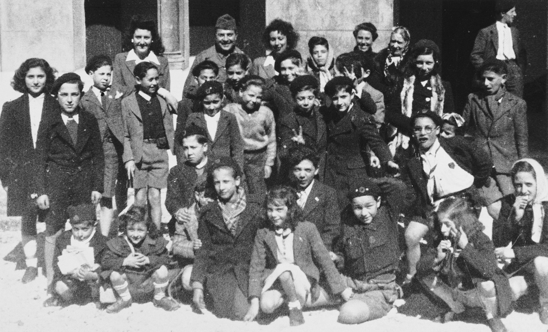 "Group portrait of Jewish children and adults outside the synagogue in Marseilles where an American Jewish chaplain is organizing Passover religious services.  The original caption reads, ""For many -- their first Passover in freedom."""