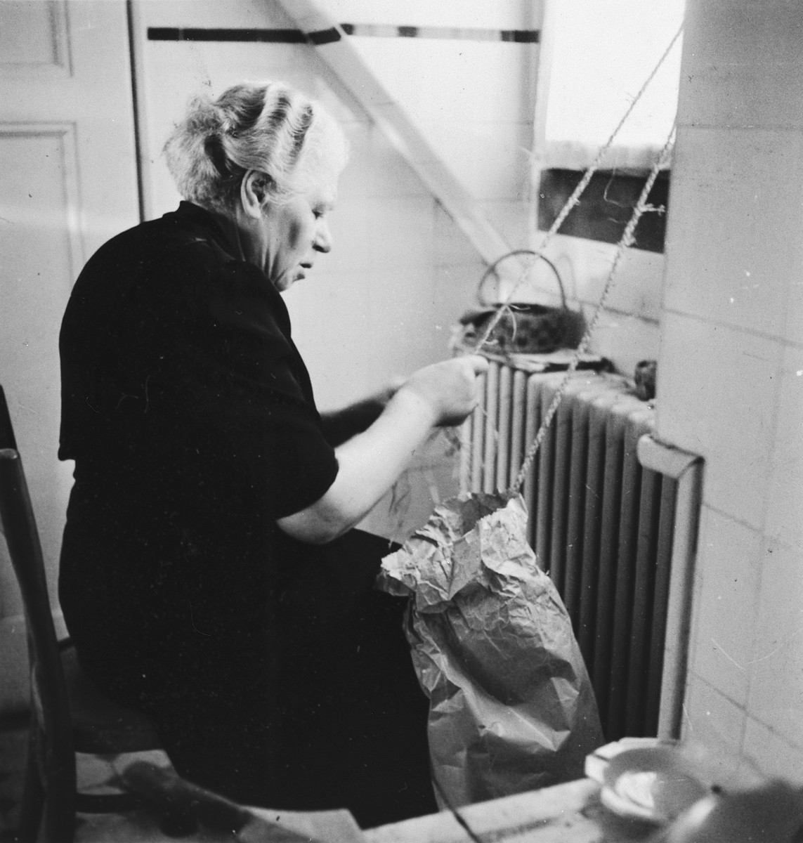A Jewish refugee braids rope in her apartment in Switzerland.  Pictured is Renate Hirsch, the grandmother of the donor.