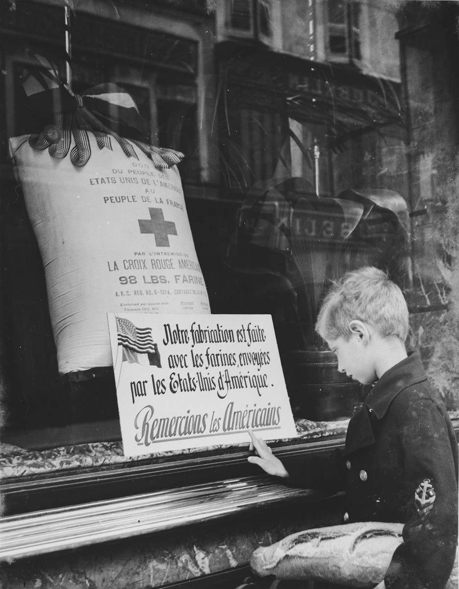 A young boy carrying a loaf of bread under his arm looks at a large sack of flour in the window of a Red Cross food distribution center emblazoned with a sign thanking the American people for their support of the people of France.  The photographer Walter Limot took this photograph of his son, Andre, at the bequest of the Red Cross.