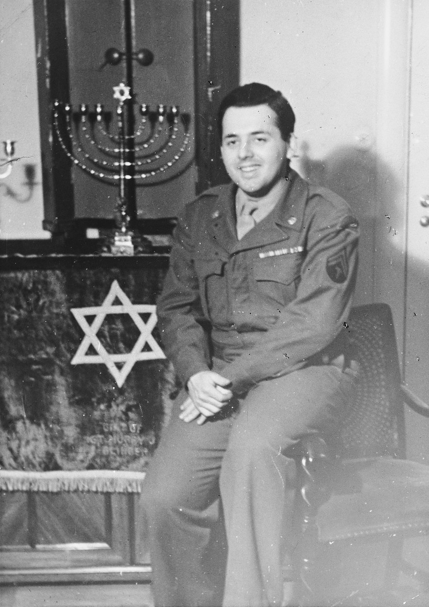 """Close-up portrait of Saul Loeb, a Jewish chaplain's assistant, sitting in front of the Torah ark and menorah in the Berlin Chaplain's center.  The original caption reads, """"Another picture taken in front of our Ark -- the ark was made especially for Chaplain Shubow by a Jewish architect from Holland, and he carried it in his jeep for services at the front during combat."""""""