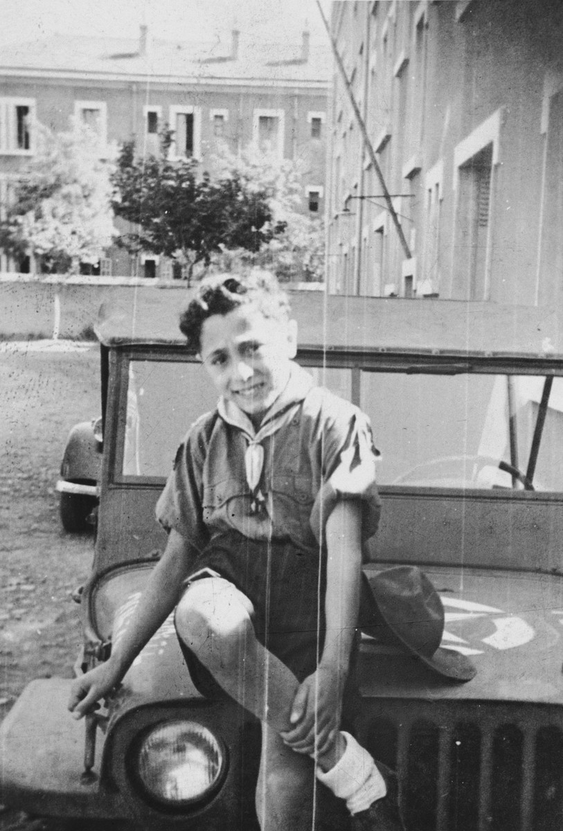 """A Jewish boy scout poses on the hood of a jeep outside the American military base in Marseilles.  The original caption reads, """"Jo-Jo, the little Jewish boy scout who comes to see me at the office, taken in front of the office at DBS headquarters."""""""