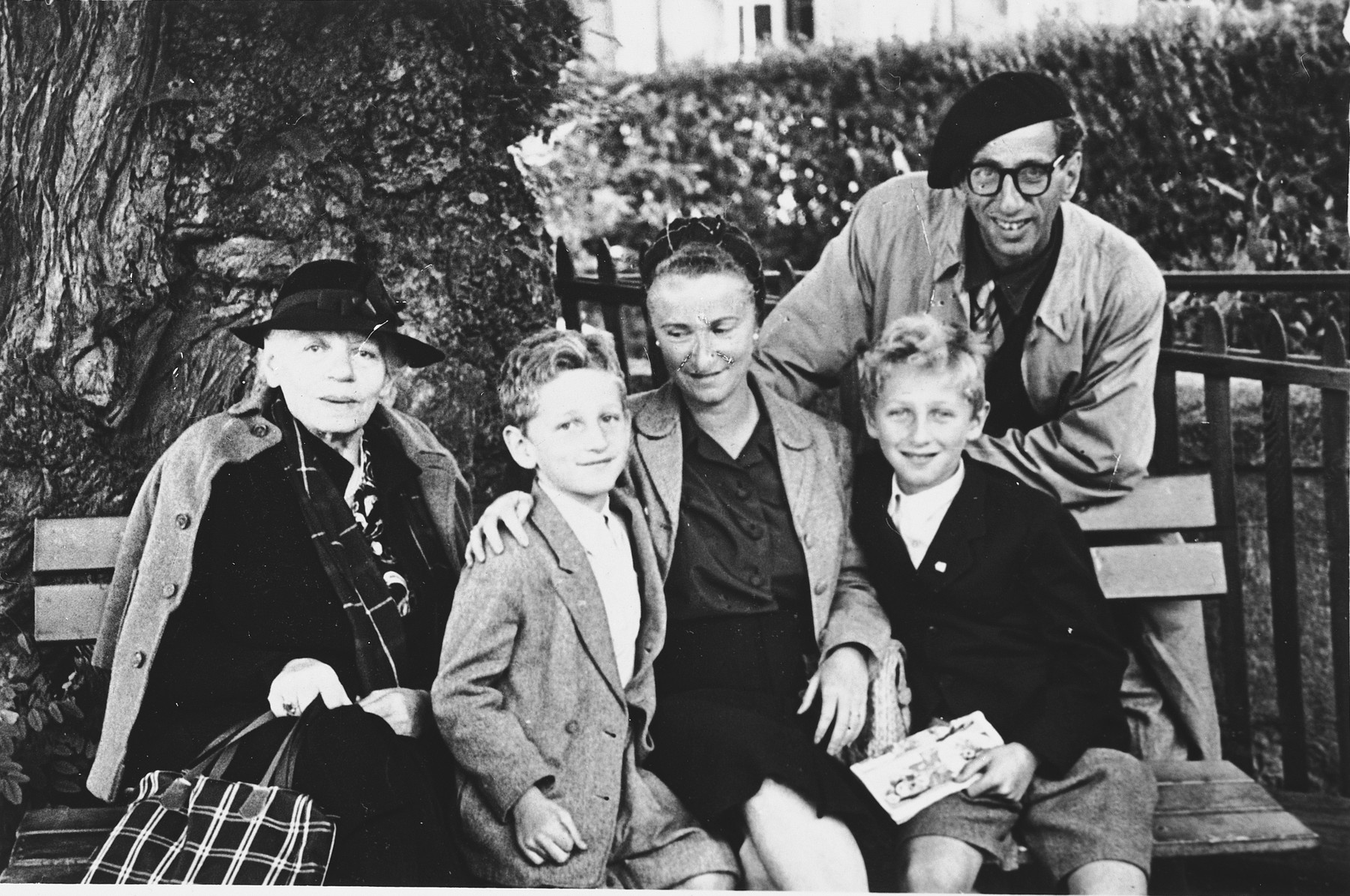 Group portrait of a Jewish refugee family seated on a park bench in Geneva.  From left to right are Renate Hirsch, Claude, Ines Walter and Andre Limot.