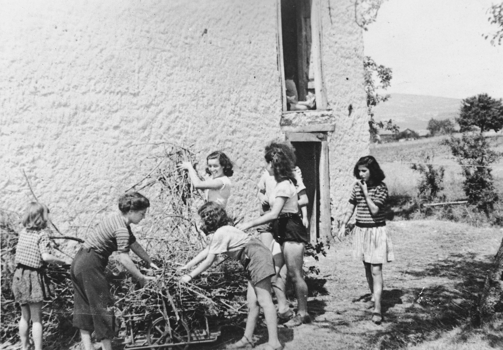 Jewish children gather up sticks outside an OSE children's home [perhaps La Forge in Fontenay-aux-Roses].