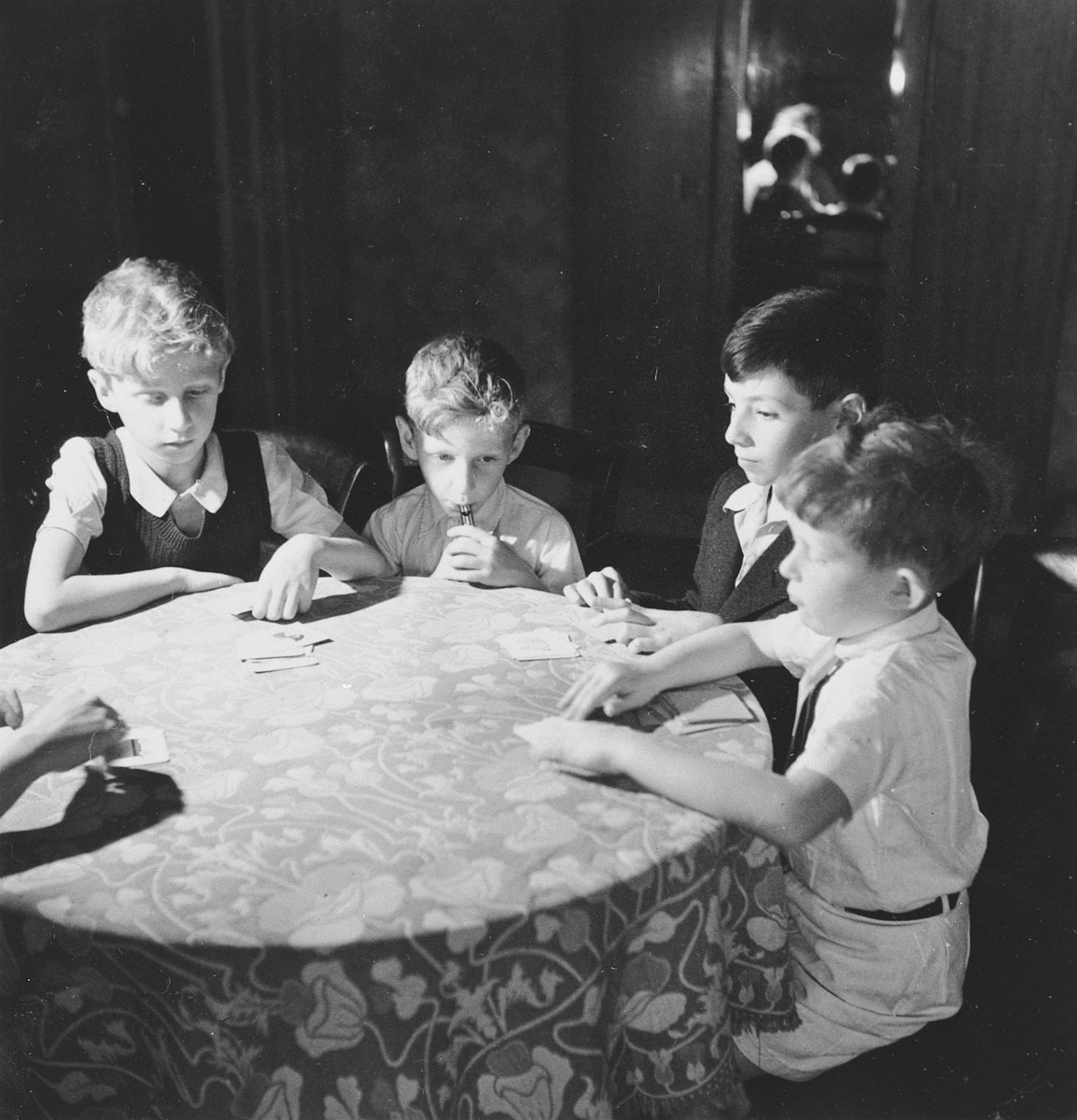 Four Jewish children sit around a table and play a card game in their apartment in Geneva, Switzerland.  Among those pictured are Andre (far left) and Claude Limot (second from left).
