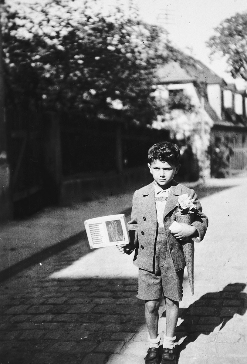 A Jewish-Czech boy poses with a cone and book on his first day of school.  Pictured is Alexandre Fischler.