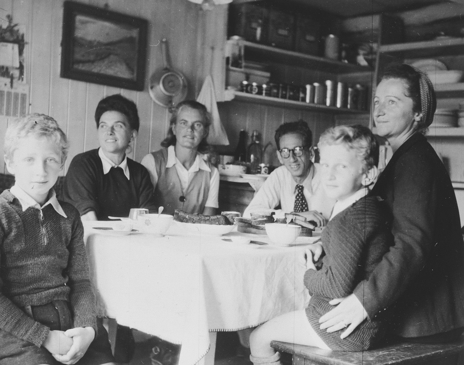 Jewish refugees gather around a table in their apartment in Geneva.  Among those pictured are the photographer, Walter Limot, and his wife Ines and sons, Andre and Claude.