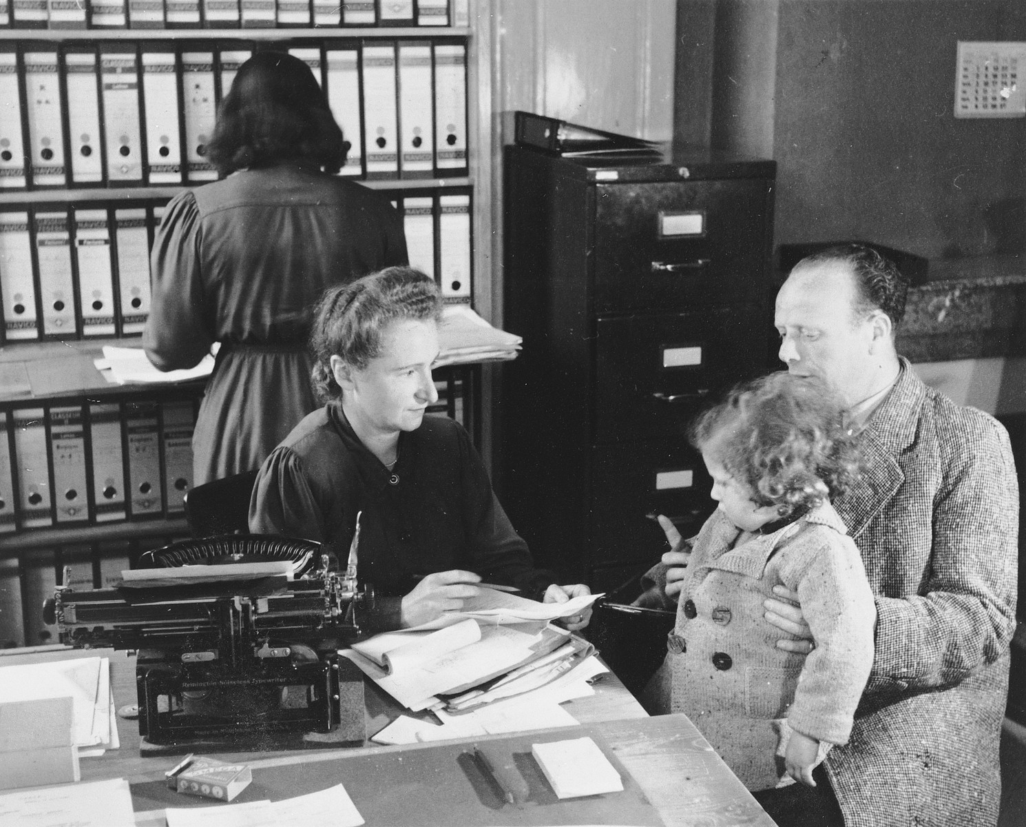 A woman, herself a refugee from France, assists a gentleman with a young child on his lap, in the offices of Secours aux Refugies in Geneva, Switzerland.  Seated at the desk is Ines Limot.