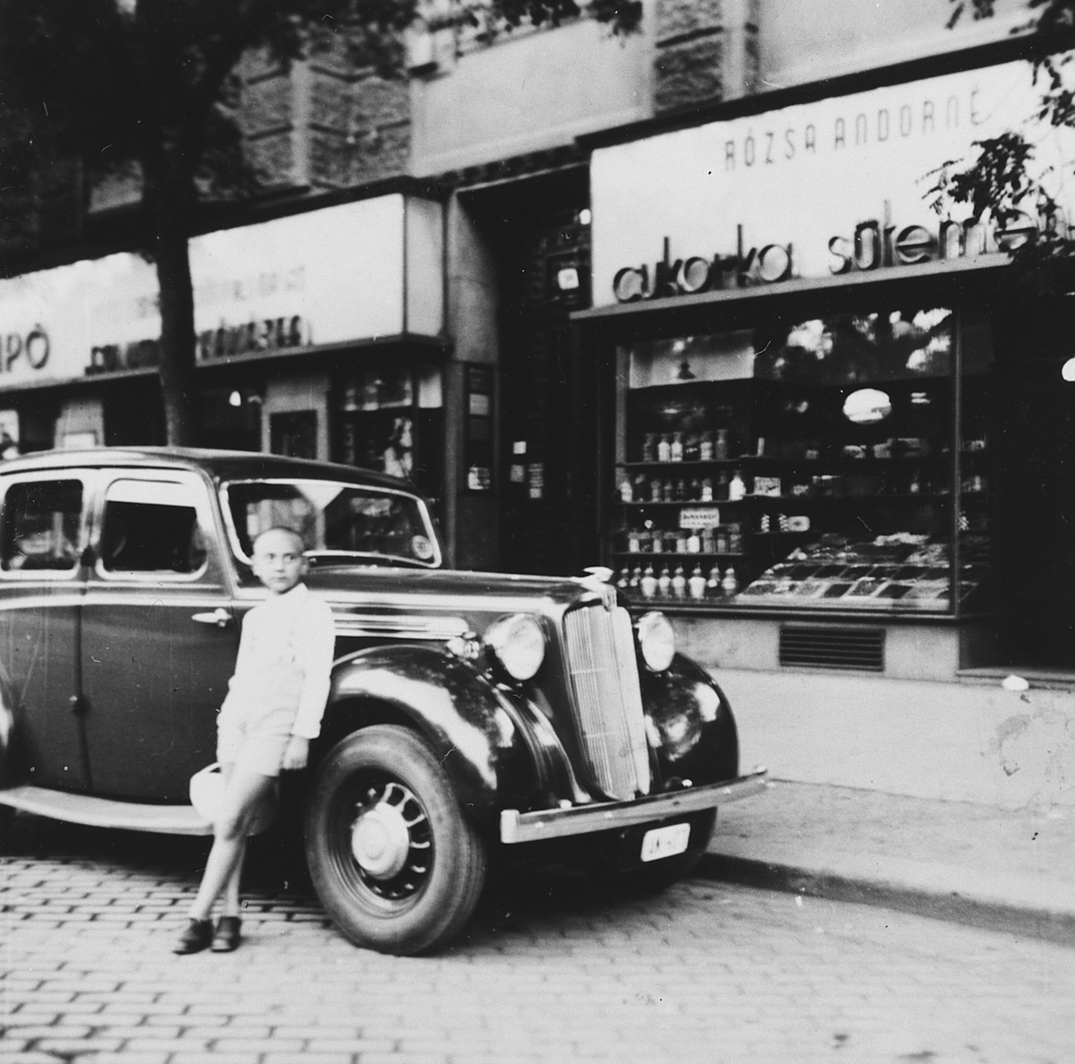 A young Jewish boy leans against an automobile parked on a commercial street in Budapest.  Pictured is Ivan Pal.