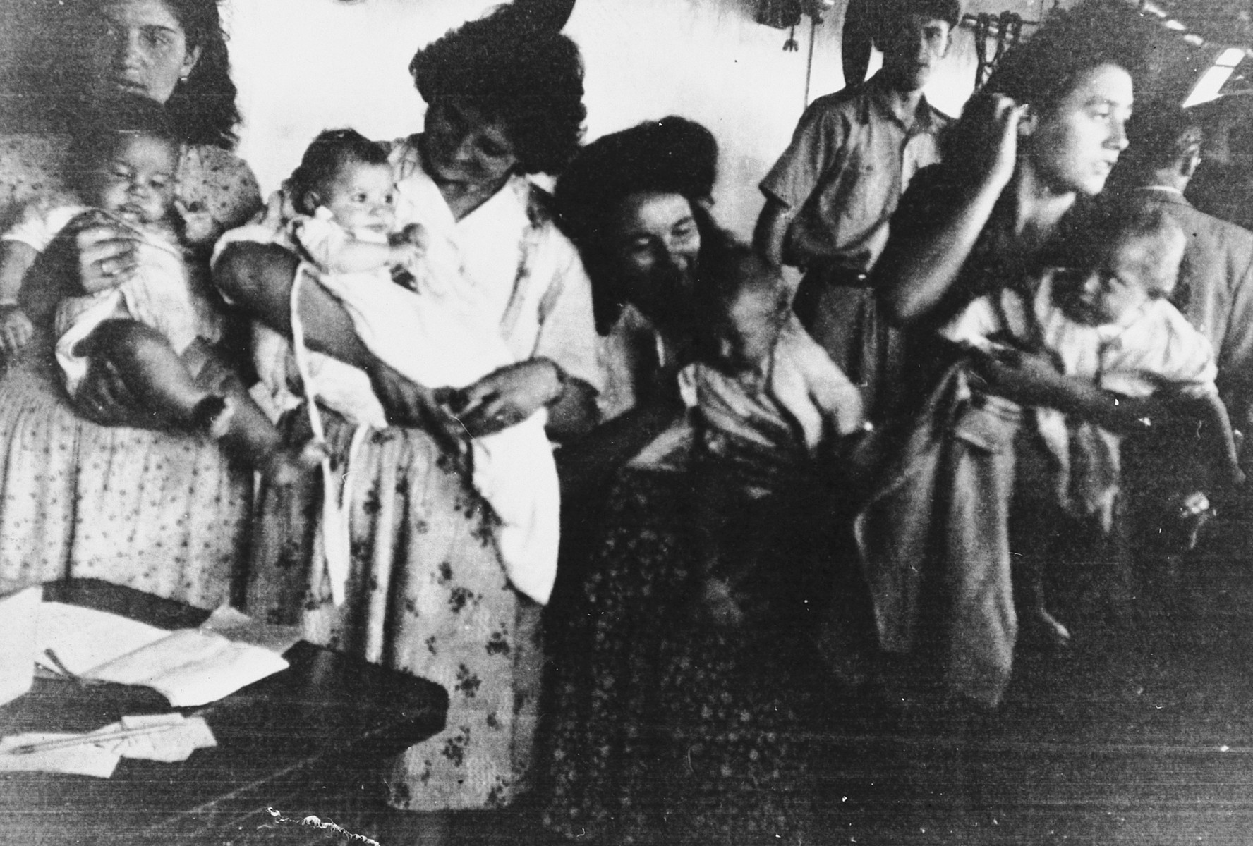 Jewish refugee women carrying infants crowd into the hull of a ship [probably the Mataroa] sailing from Marseilles to Palestine.
