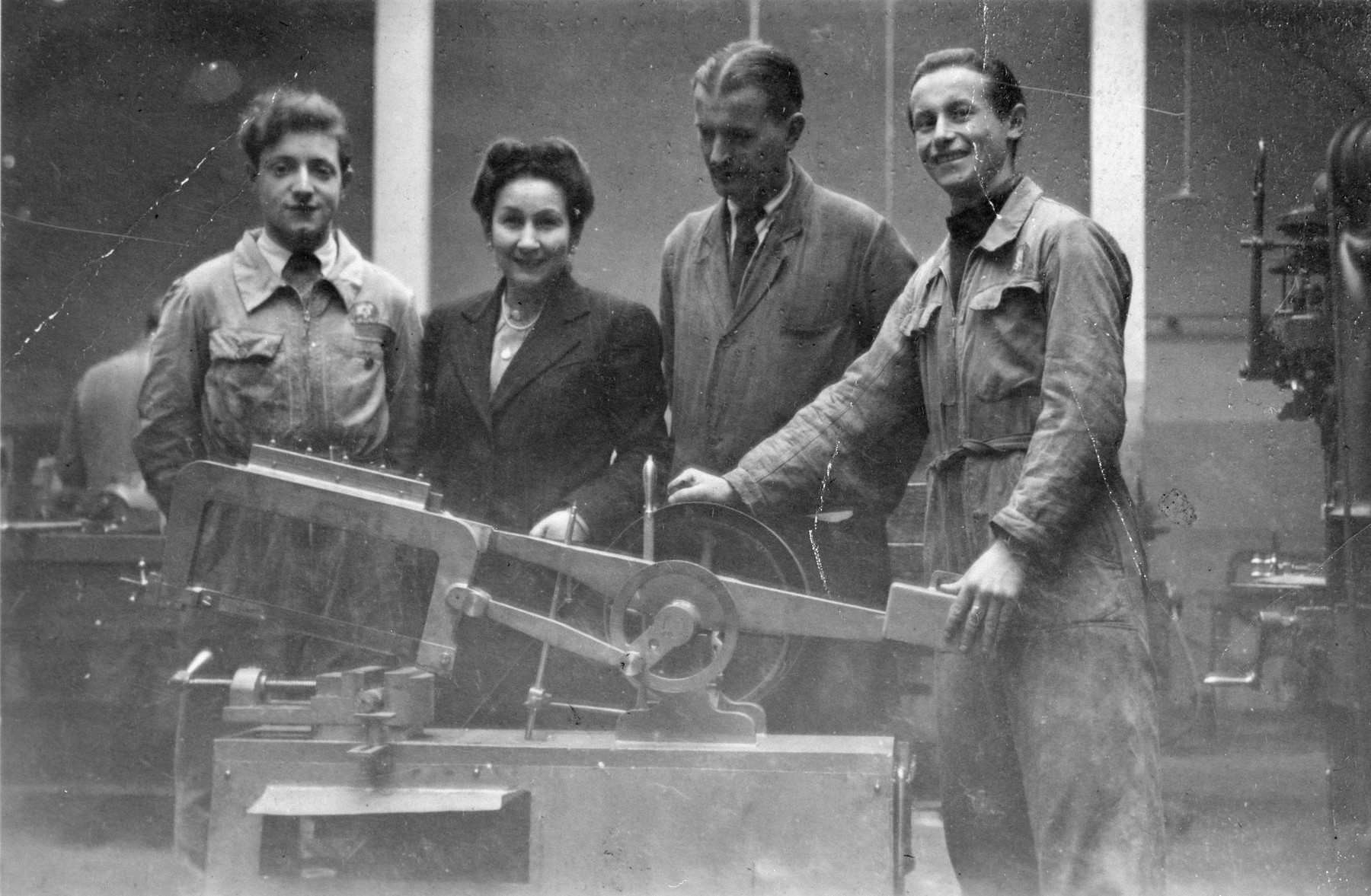 Four people pose by a piece of machinery in what probably is a vocational training school in a displaced persons' camp in Switzerland.