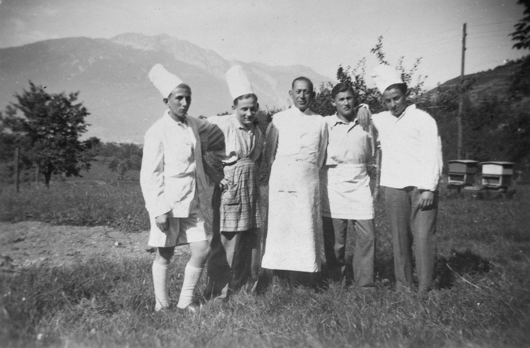 Group portrait of five men wearing chef's hats and aprons in a displaced persons' camp in Switzerland.
