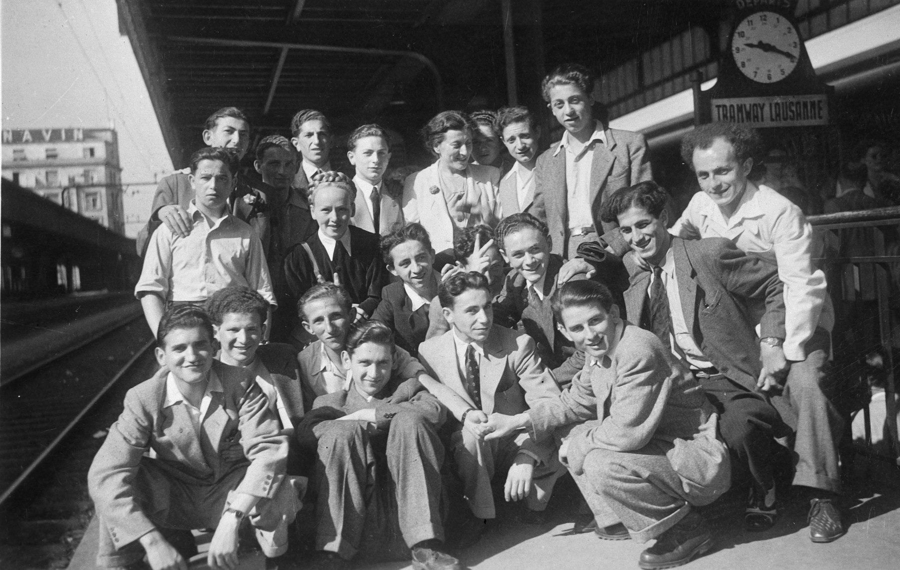 Group portrait of young Jewish survivors at a train station in Switzerland.  Among those pictured is David Gratz (Grac), standing the back row, fourth from the left.