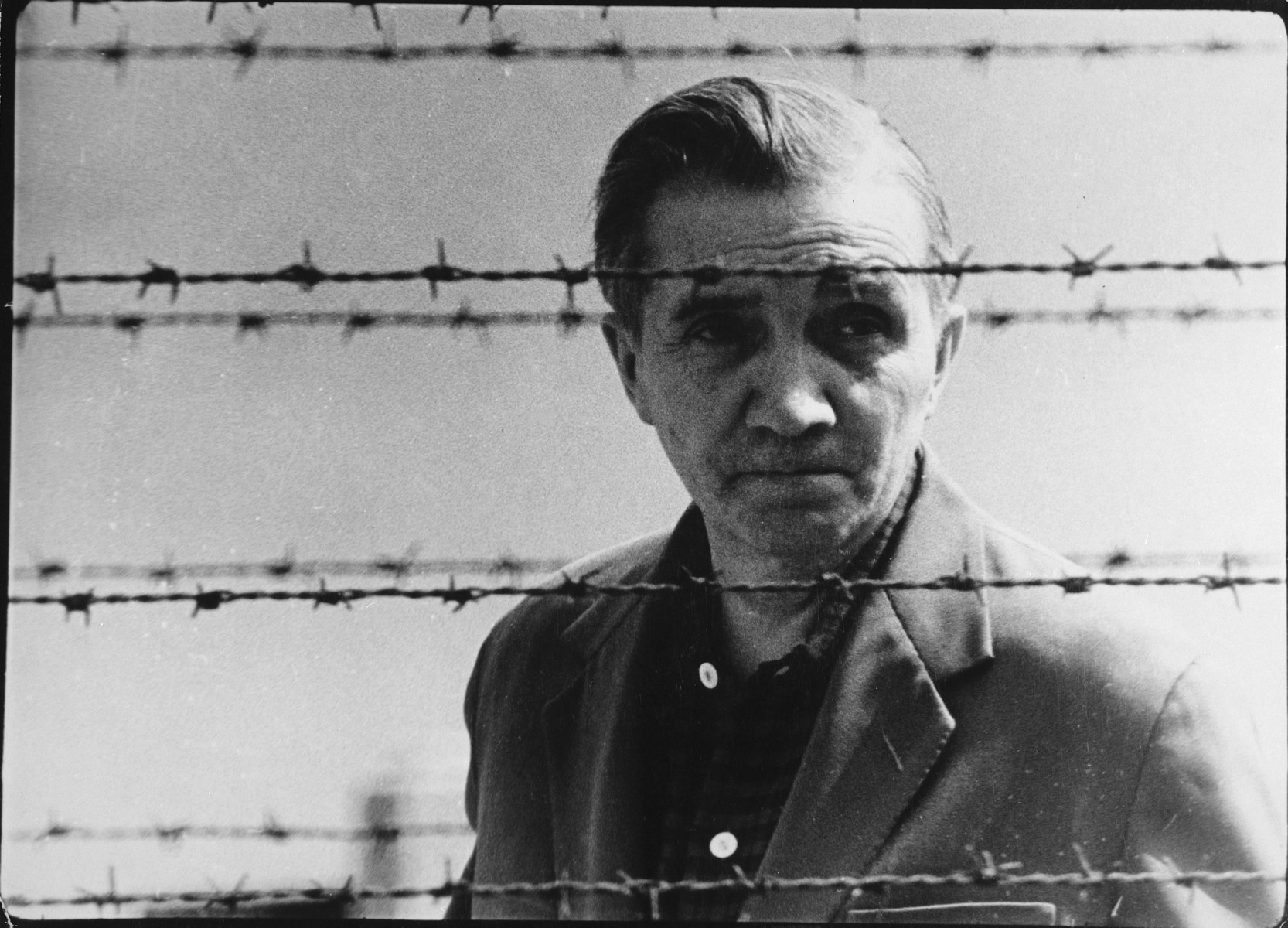 Postwar portrait of Aleksander Kulisiewiecz, Polish composer and concentration camp survivor, standing behind a barbed wire fence.