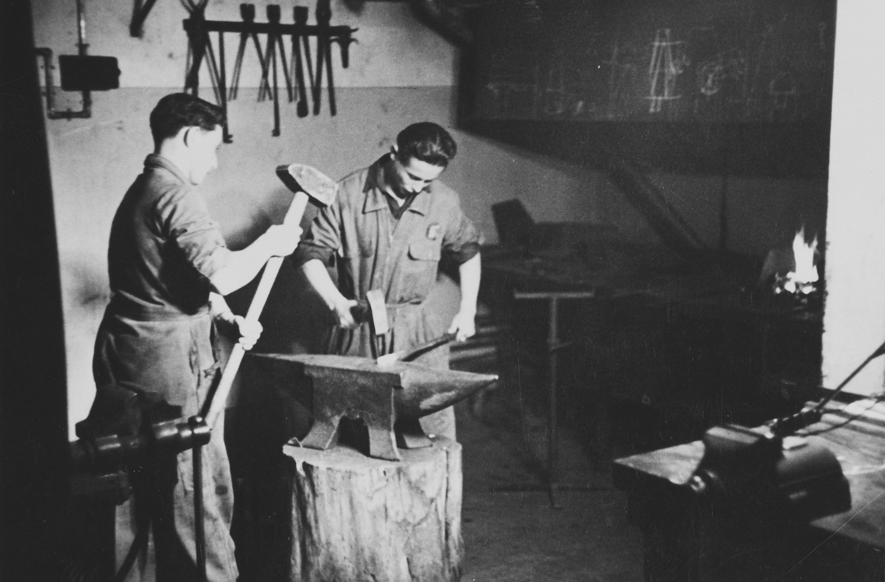 Two young Jewish survivors work in a blacksmith shop in a children's home in Switzerland.