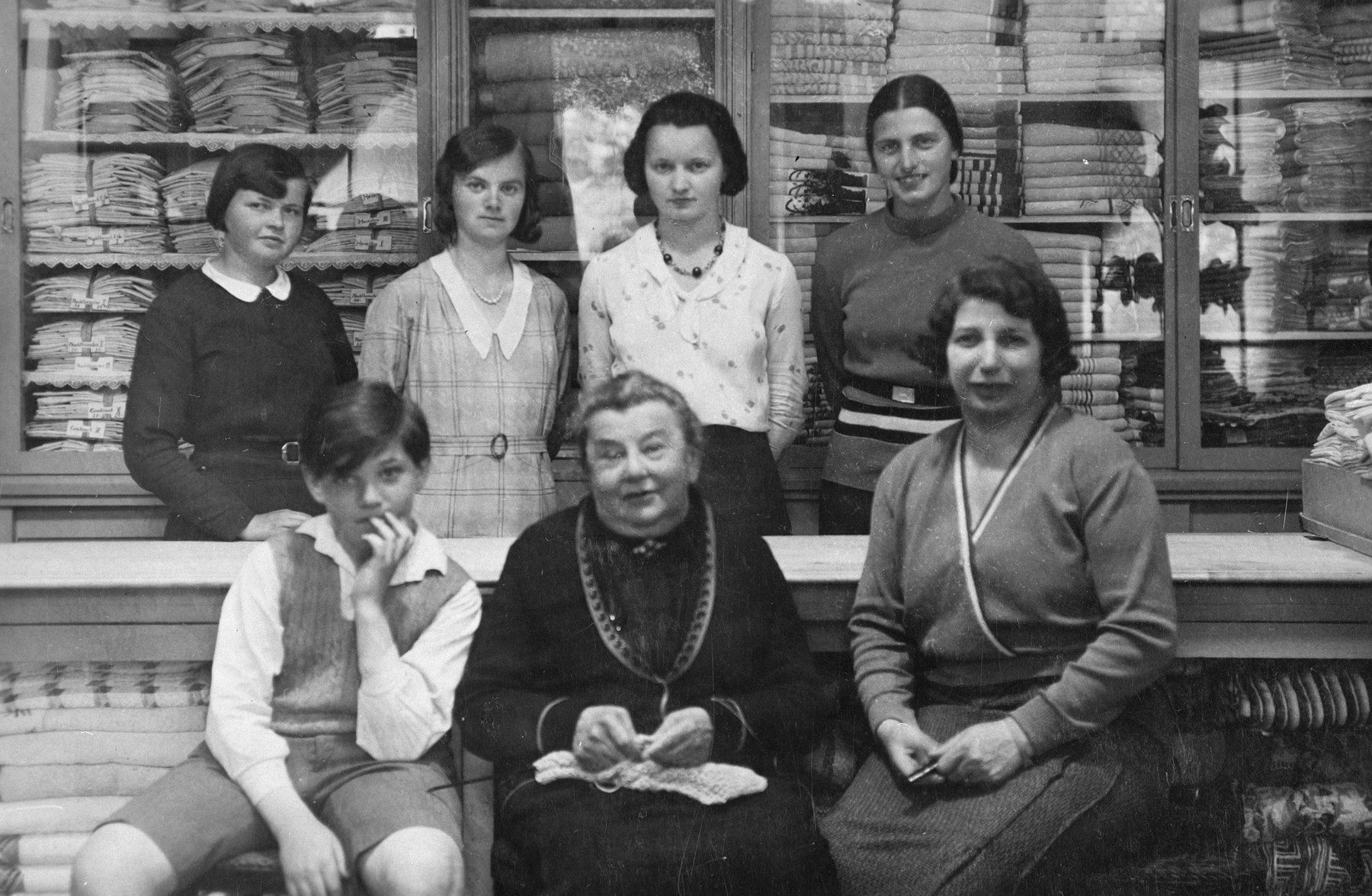 The Jewish owners of a dry goods store in Marienbad pose in front of the counter with other employees standing behind them.  Pictured in the center is Emma Kohn (grandmother of the donor) and on the right is Berta Schleissner (mother of the donor).