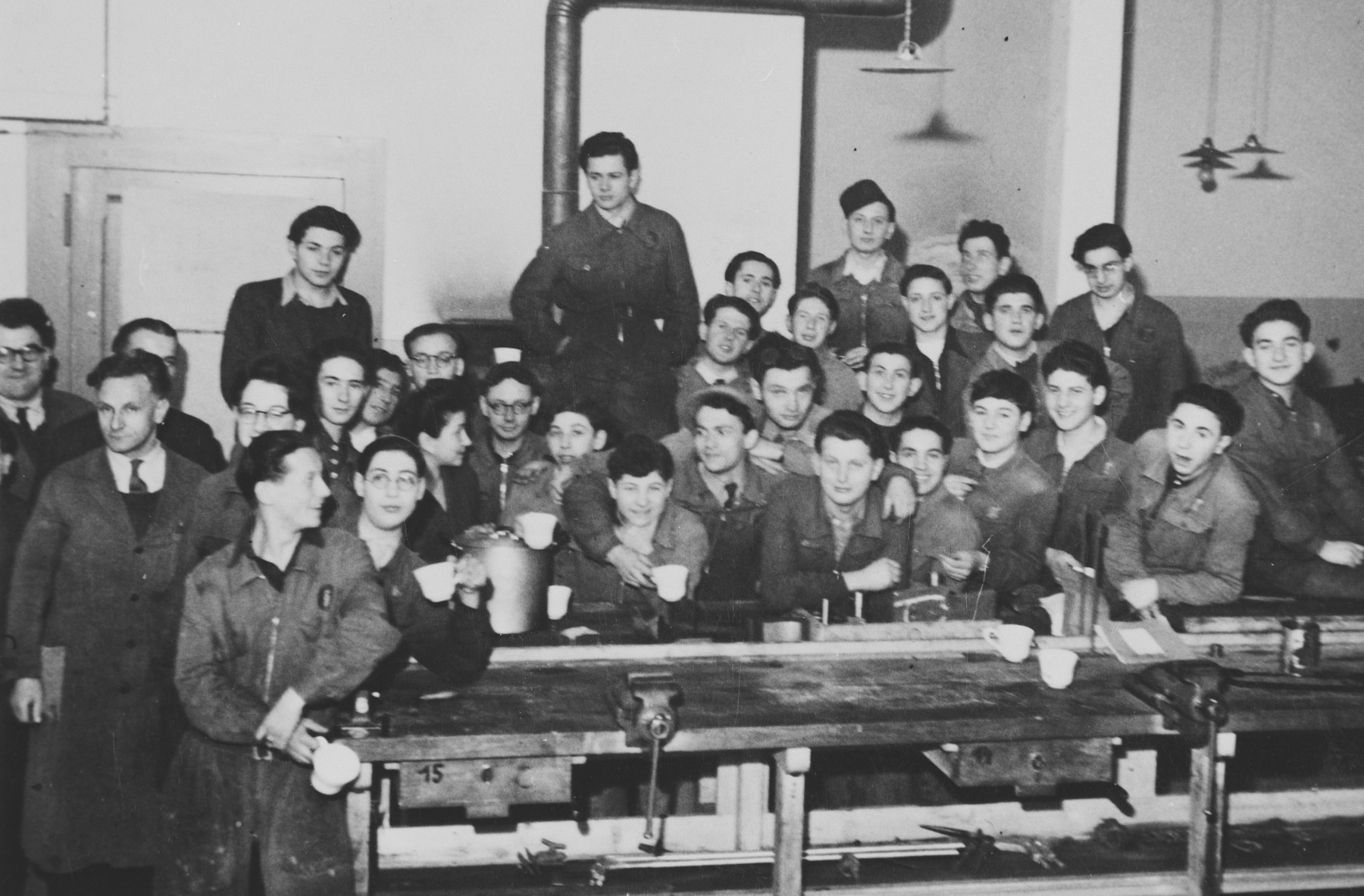 A large group of Jewish youth gather behind a piece of machinery in what probably is a vocational training school in a children's home in Switzerland.