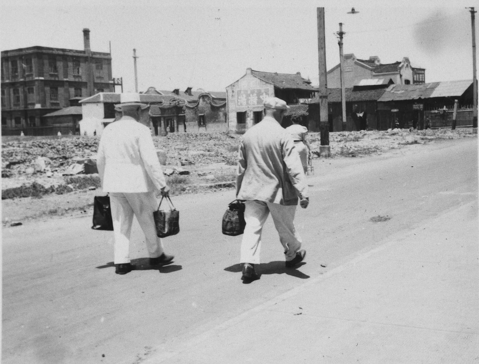 "Two men walk down a street in Shanghai carrying packages of food.   The original caption reads ""Das Essen wird nach Hause getragen."""
