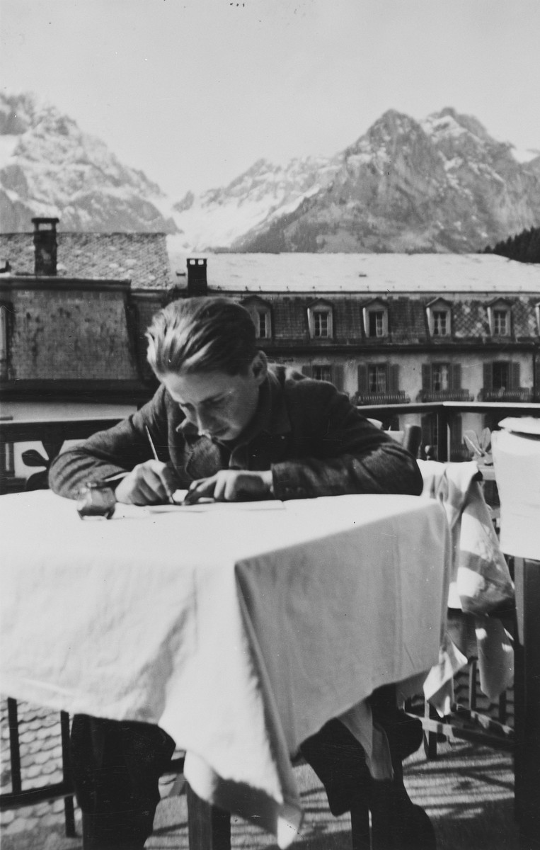A young Jewish man writes at a table in a children's home in Switzerland.  The snow capped Alps can be seen in the background.