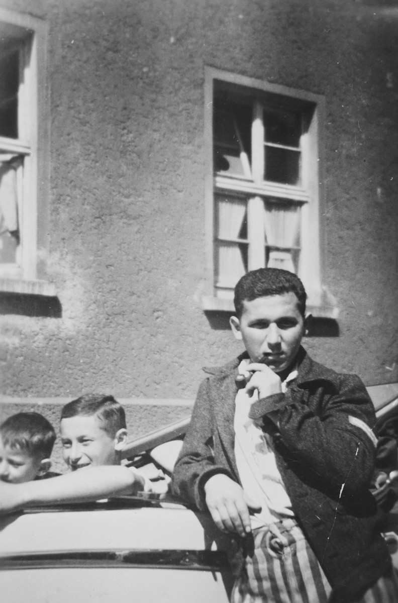 Three young survivors pose by an automobile in the Buchenwald concentration camp shortly after liberation.