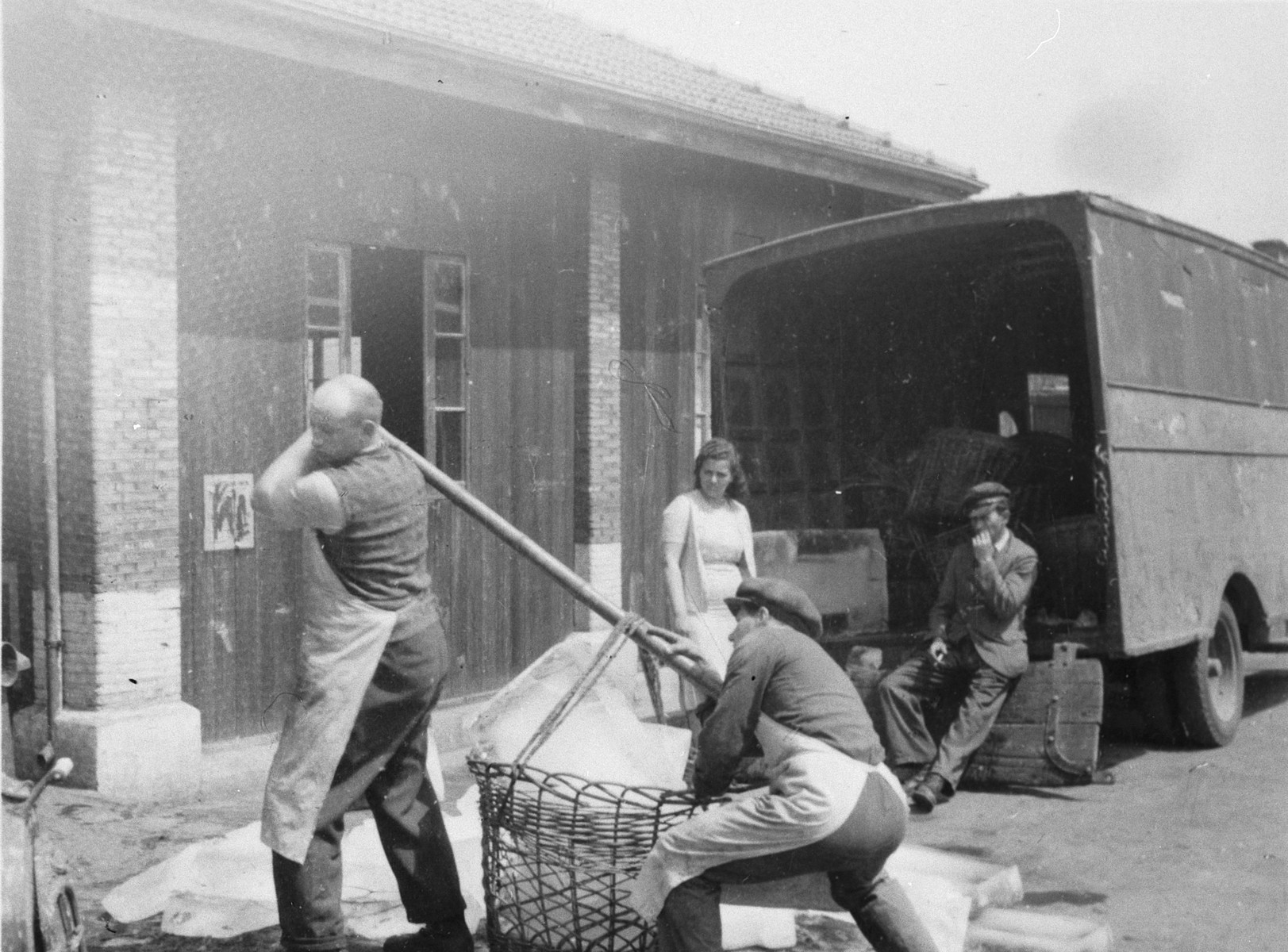 Two men wearing aprons haul a heavy basket that has been unloaded from a nearby truck in Shanghai.