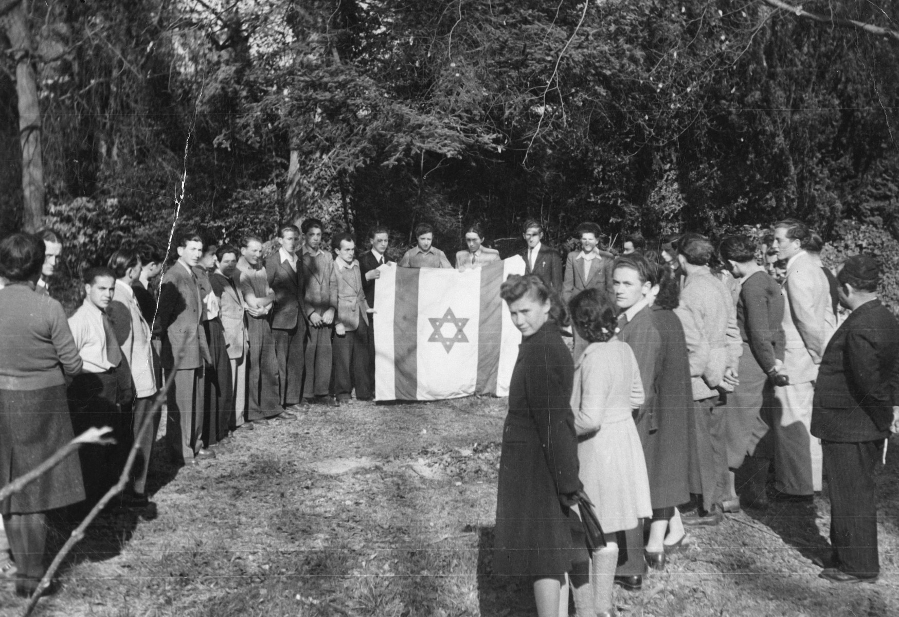 Jewish youth gather for a ceremony around a large Zionist flag in a children's home in Switzerland.  Moniek Szmulewicz is among those pictured.  Monek  Goldfinger is standing on the far right in a light colored suit.