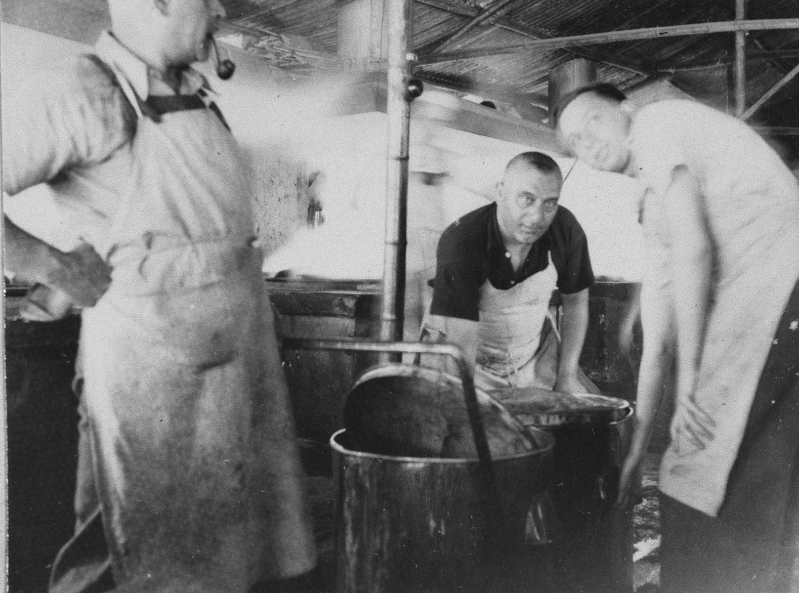 "Three men move large pots for distribution in a public kitchen in Shanghai.   The original caption reads ""Fertig fur die Ausgabe."""