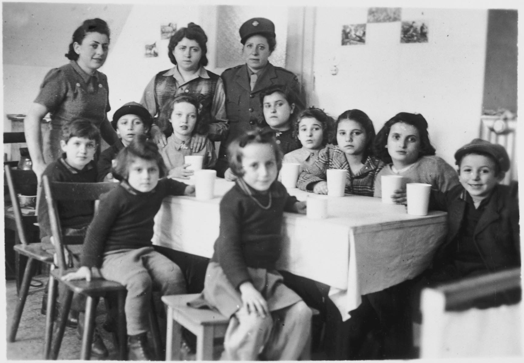 Children sit around a table set with glasses in either the Foehrenwald or the Windsheim displaced persons' camp.