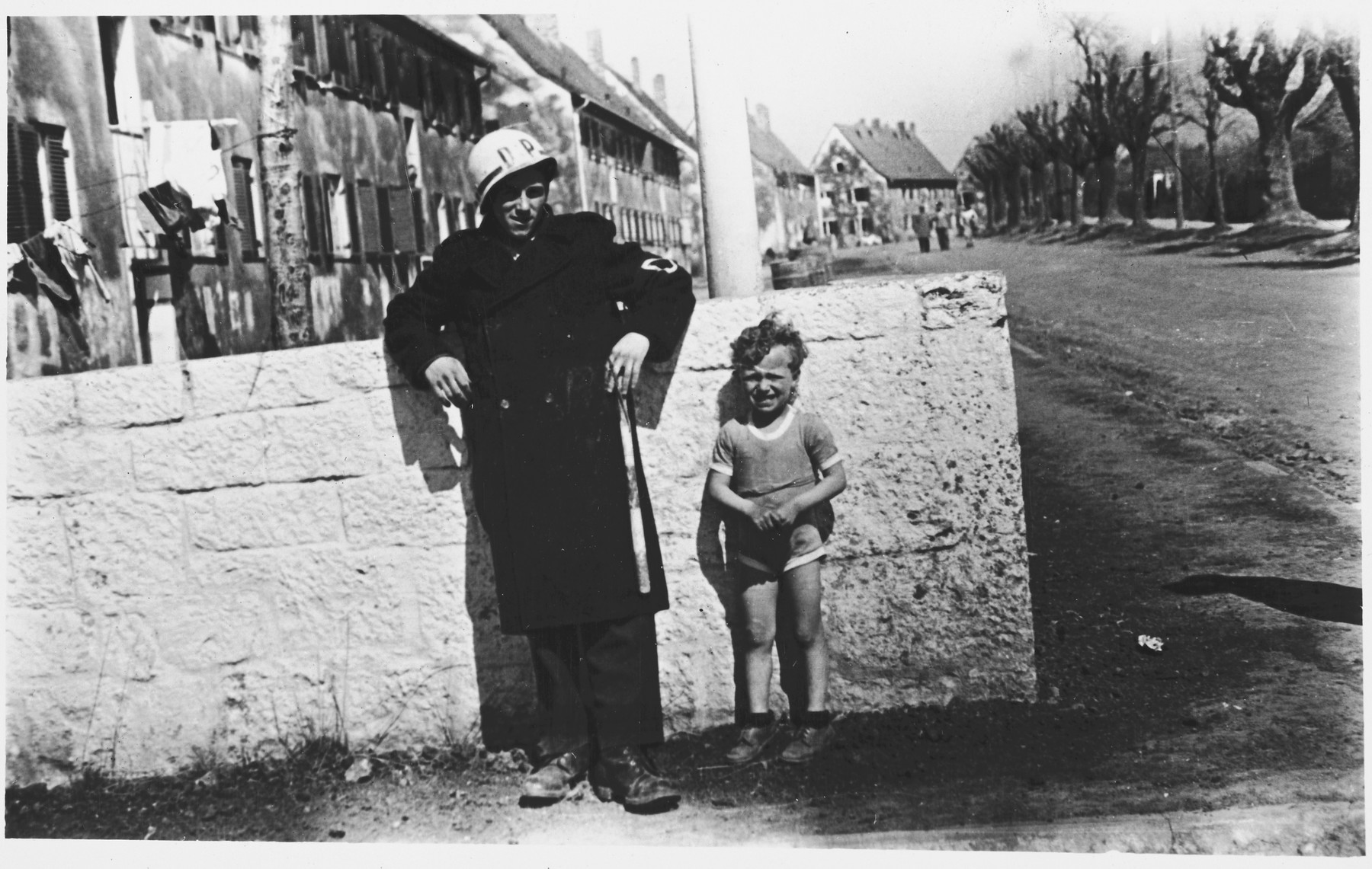 A Jewish policeman and a young boy stand against a wall in the Windsheim displaced persons' camp.