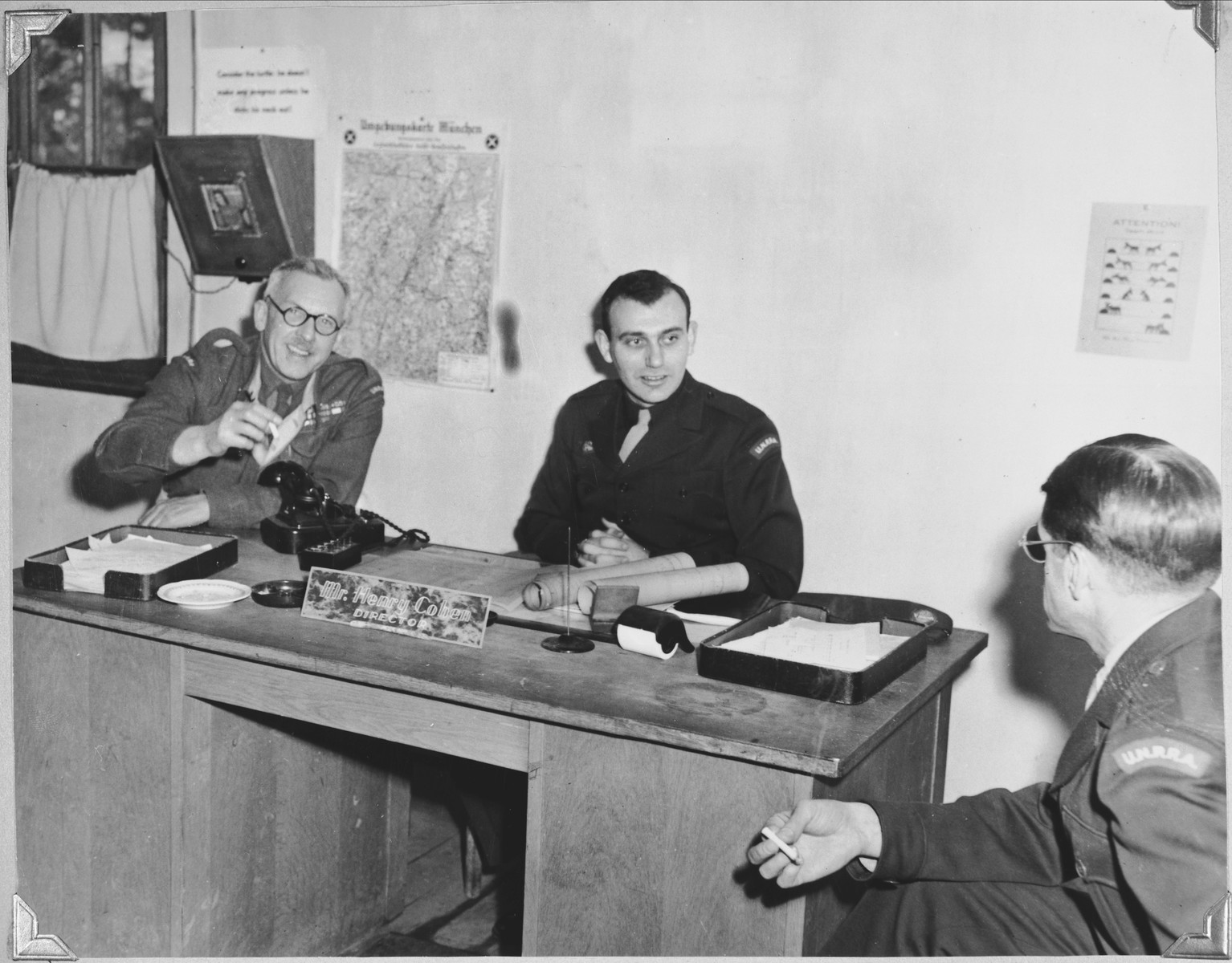 Henry Cohen, the UNRRA director of the Foehrenwald displaced persons' camp, meets with two other officers in his office.