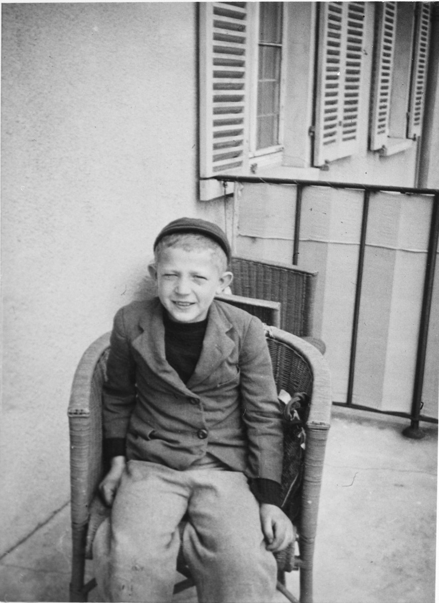 Close up portrait of a Jewish boy siting on a porch chair in the Windsheim displaced persons' camp.
