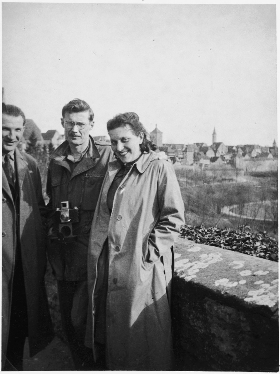 Three UNRRA workers stand against a wall near the Windsheim displaced persons' camp.  Pictured in the center is Tony Pritchard, director of the Windsheim camp and husband of the donor. Also pictured are Fred and Lydia Stern.