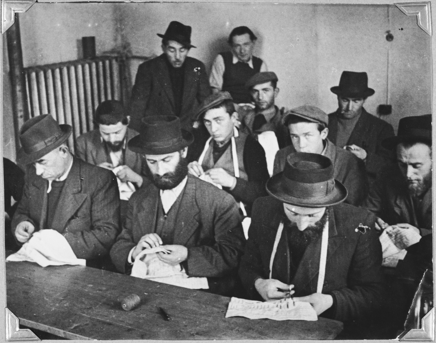 Orthodox Jewish men sew in the tailoring workshop of the Windsheim displaced persons' camp.