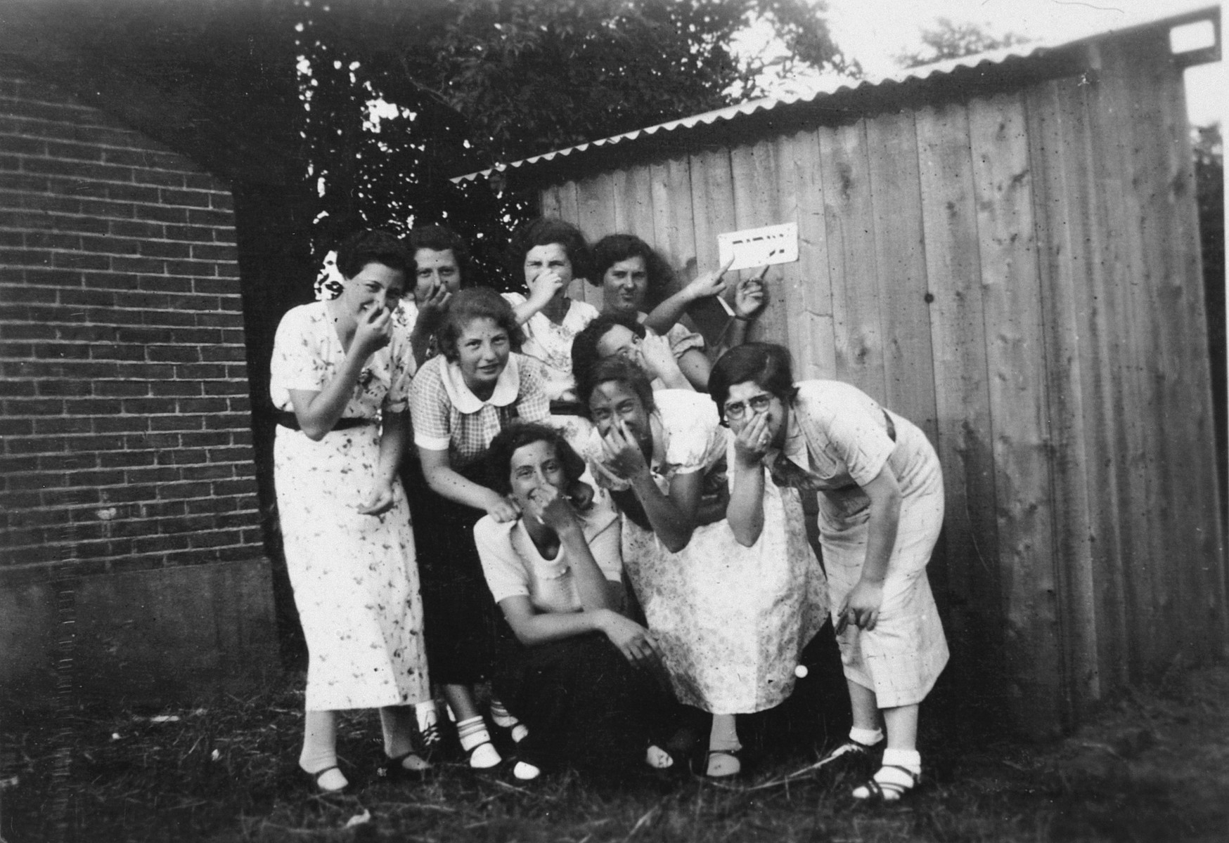 A group of young women hold their noses and point to a sign in what [probably is the Windsheim] displaced persons' camp.