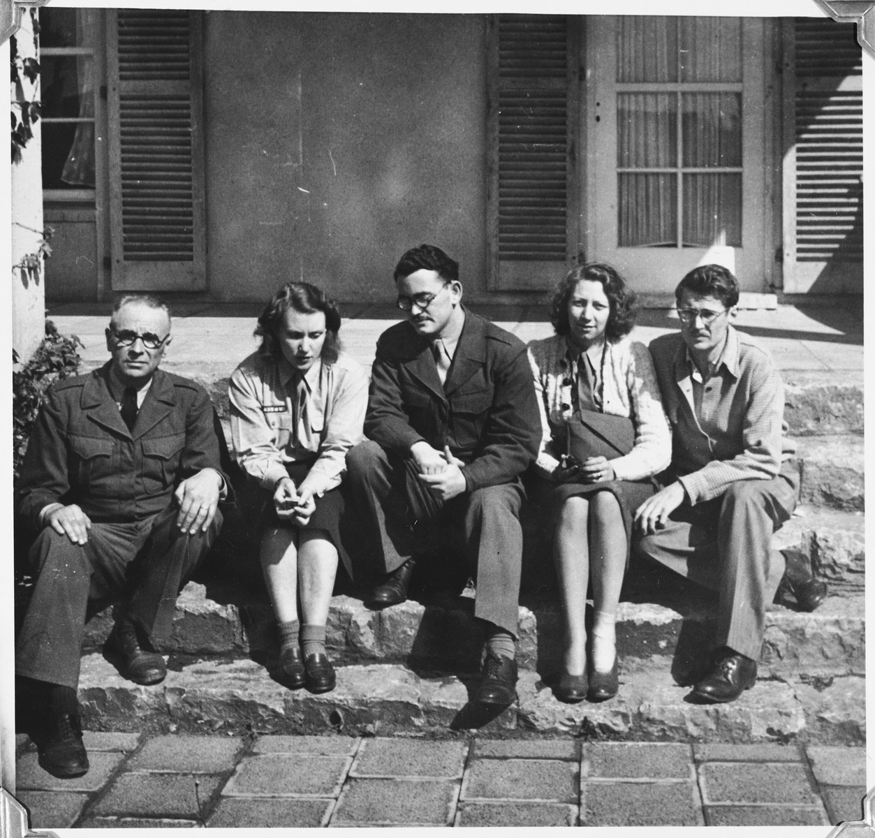 UNRRA staff of the Windsheim displaced persons' camp sit outdoors on the steps to a building .  Marion Pritchard is pictured second from the left.  Her husband Tony is on the far right.  In the center is Stanley Abramowitz.