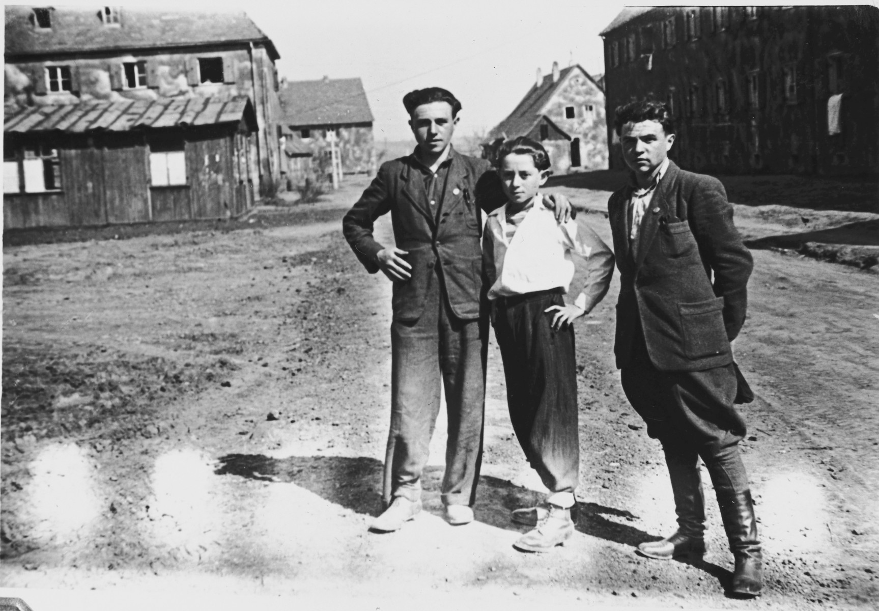 Three men pose together on a street of the Windsheim displaced persons' camp.