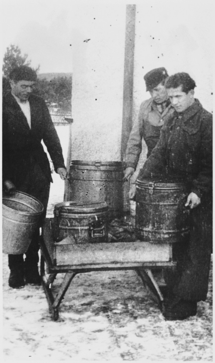 Three men lift large barrels in what [probably is the Windsheim] displaced persons' camp.
