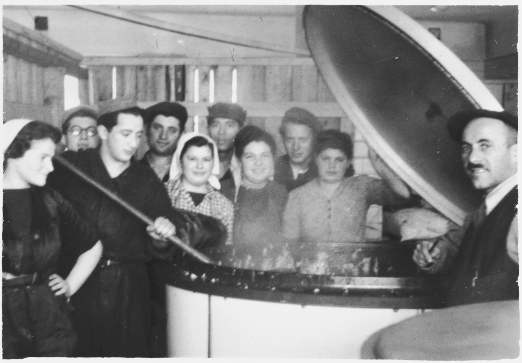 Group-portrait of workers in the kosher kitchen surrounding a large vat in what [probably is the Windsheim] displaced persons' camp.