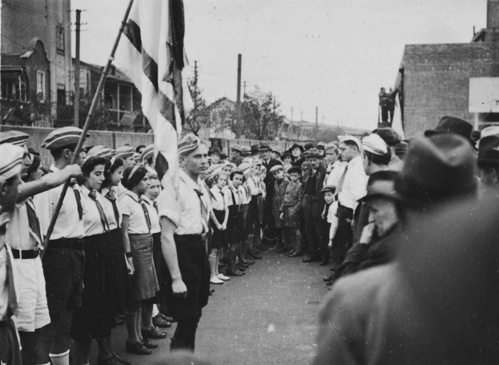 Zionist youth in Shanghai gather in formation with a flag.