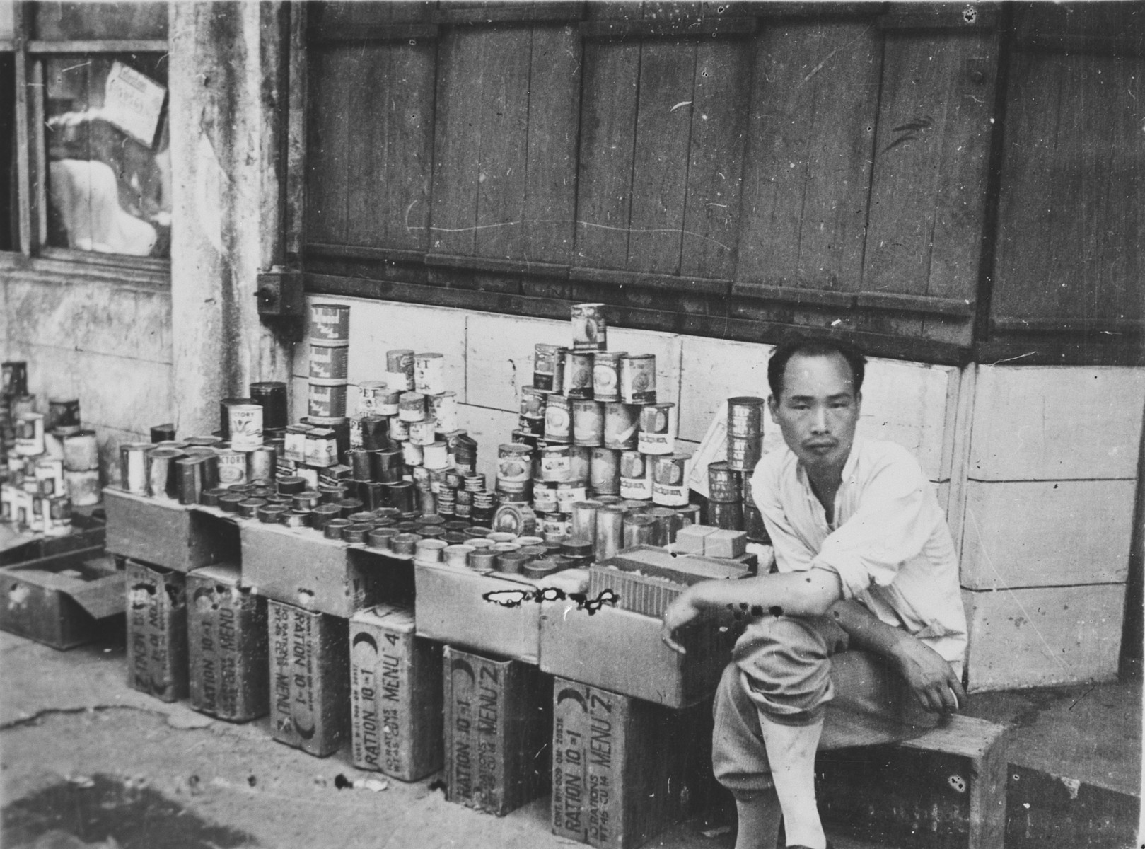 A Chinese merchant sits next to his wares on a sidewalk in Shanghai.