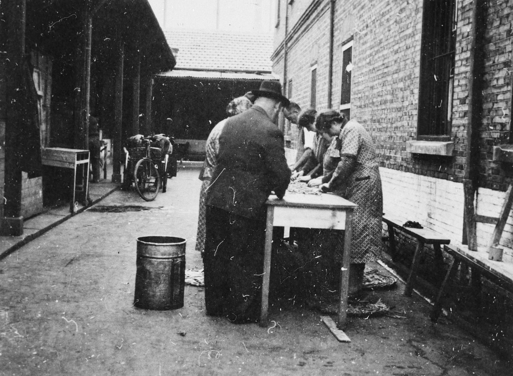 "Men and women clean vegetables in an outdoor kitchen in Shanghai.  The original caption reads ""Gemueseputzen""."