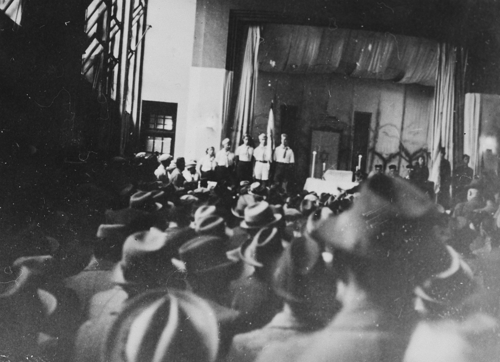 "A large crowd attends a memorial service for the first anniversary of Kristallnacht in a synagogue in Shanghai.  The original caption reads ""Gedachtnisfeier."""