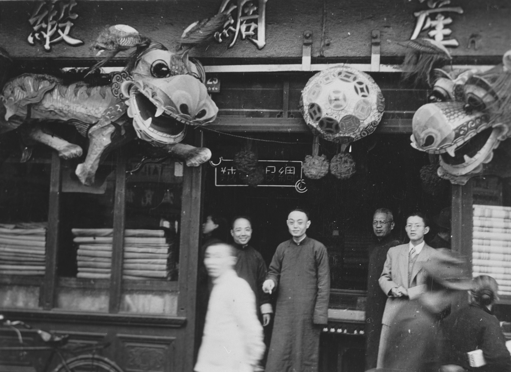 Chinese merchants stand outside their shop in Shanghai.