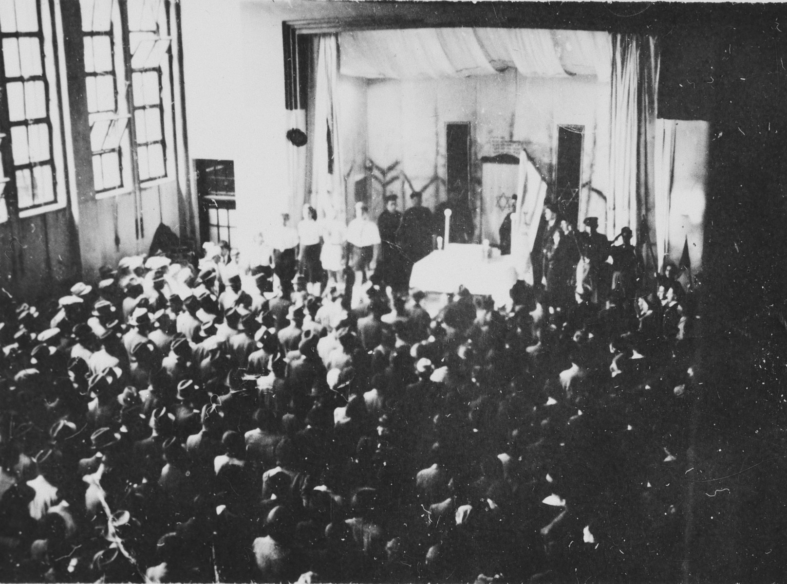 A large crowd attends a memorial service for the first anniversary of Kristallnacht in an auditorium in Shanghai.