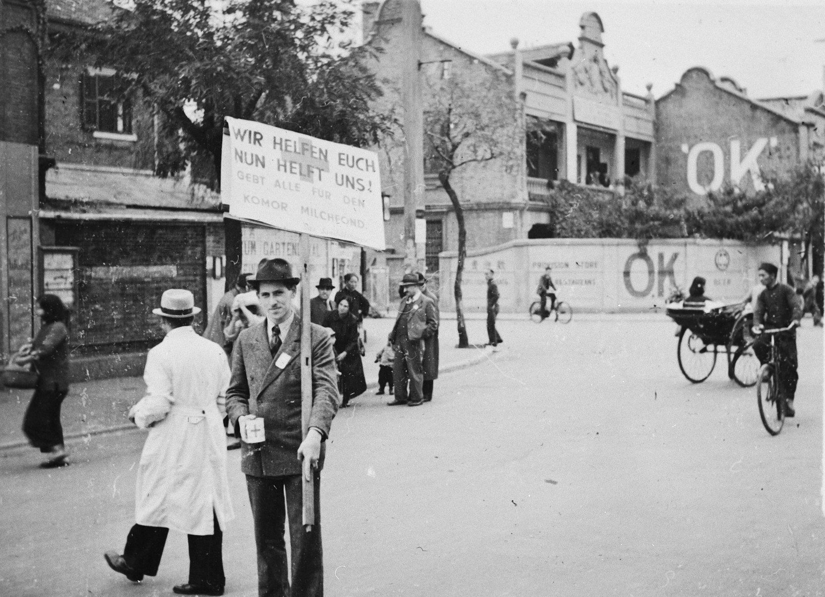 "A man walks down a street in Shanghai carrying a poster to collect money for the milk fund.  The original caption reads ""Sammlung fur den I.C. Milchfond."""