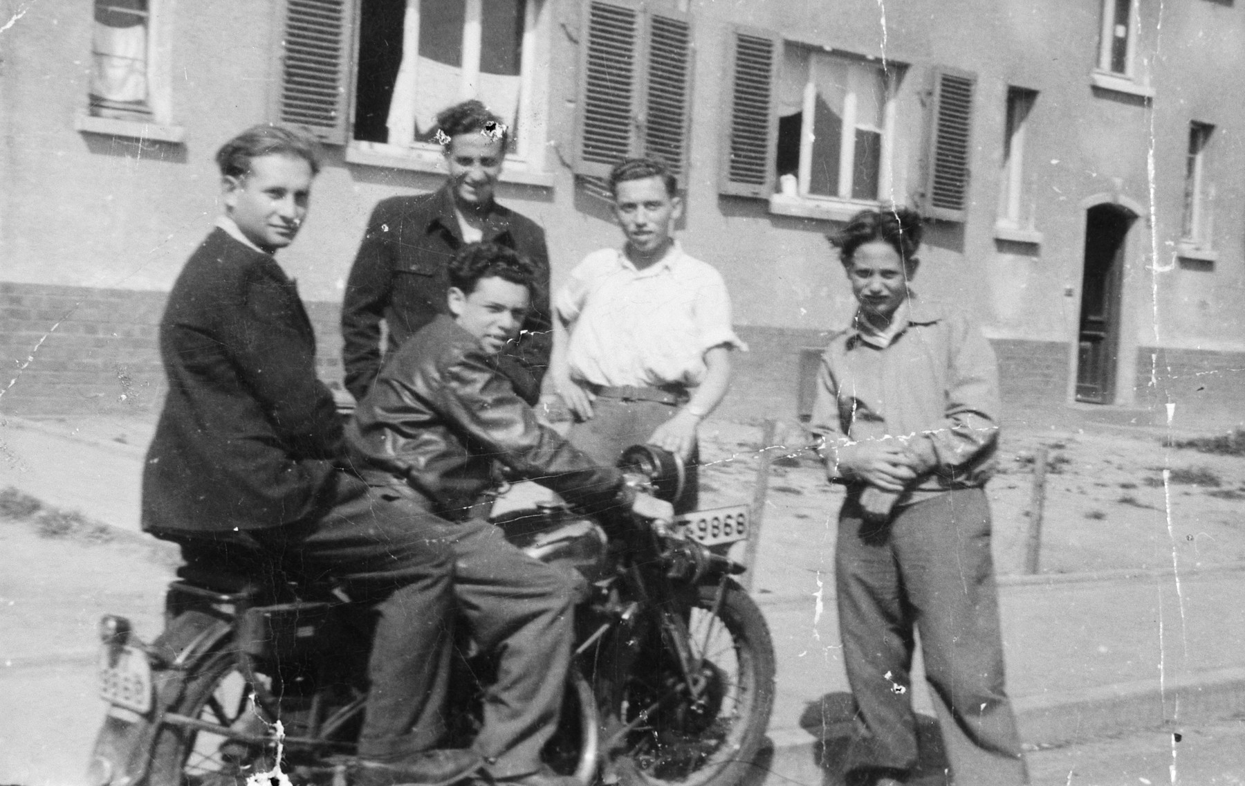 Five young men pose on or next to a motorcycle in the Zeilsheim displaced persons' camp.  Standing second from the left is Chuna Grynbaum.  Alex Herblum is on the motorcycle.