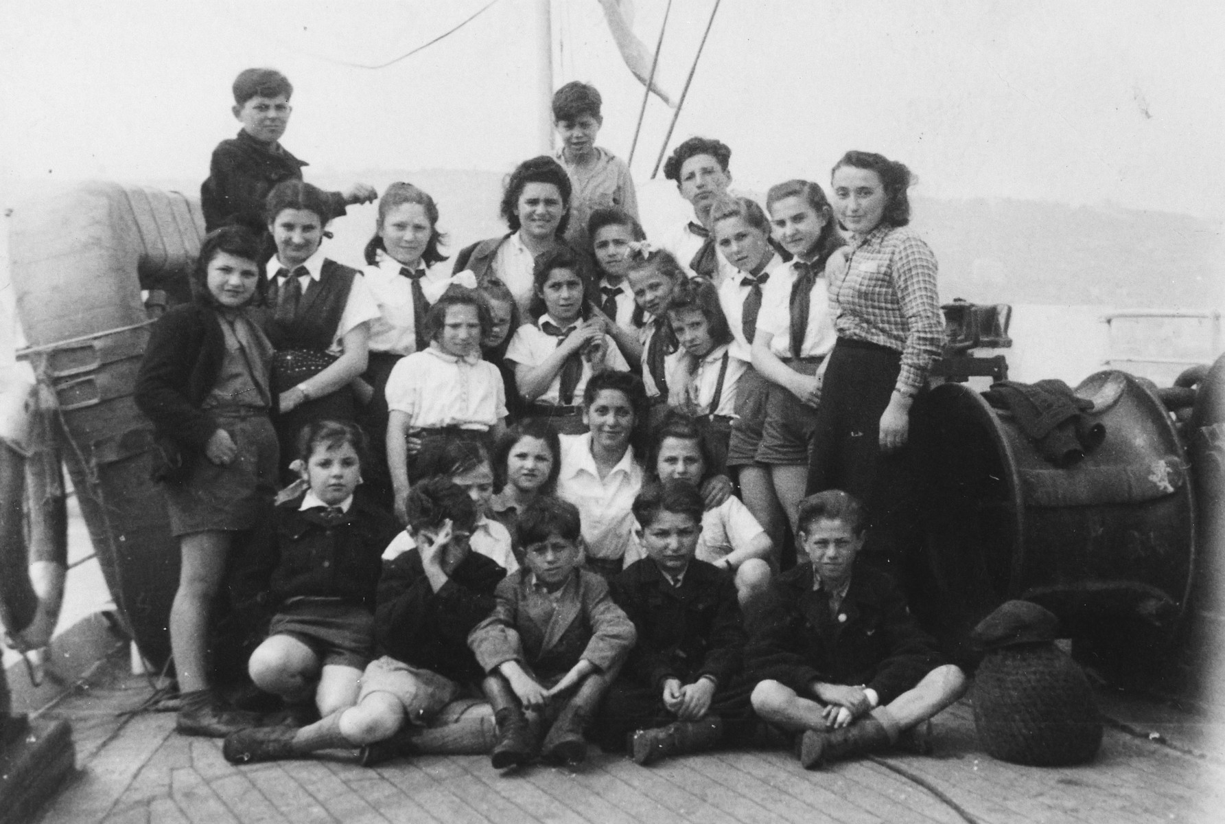 Group portrait of Jewish children en route to Palestine on board the Kedma.  Pictured with them is their counselor, Esther Menaker (center).