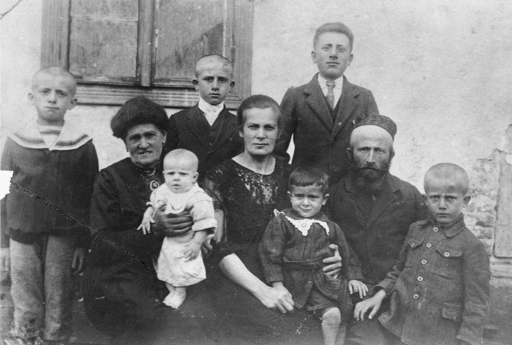 Portrait of a religious Jewish family in Lvov.  Pictured are Jakow and Szprinca Menaker and their chldren.  Ephraim is on his mother's lap, third from the right.