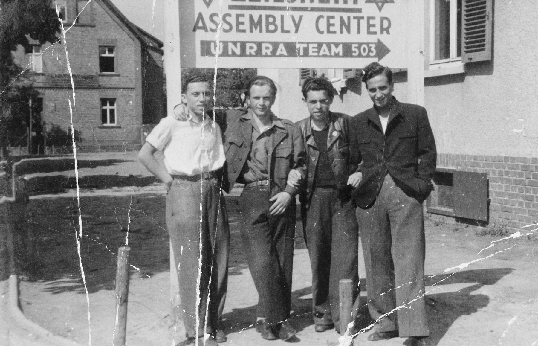 Four young Jewish men stand in front of an UNRRA Assembly Center sign in the Zeilsheim displaced person's camp.  Chuna Grynbaum is on the far right.