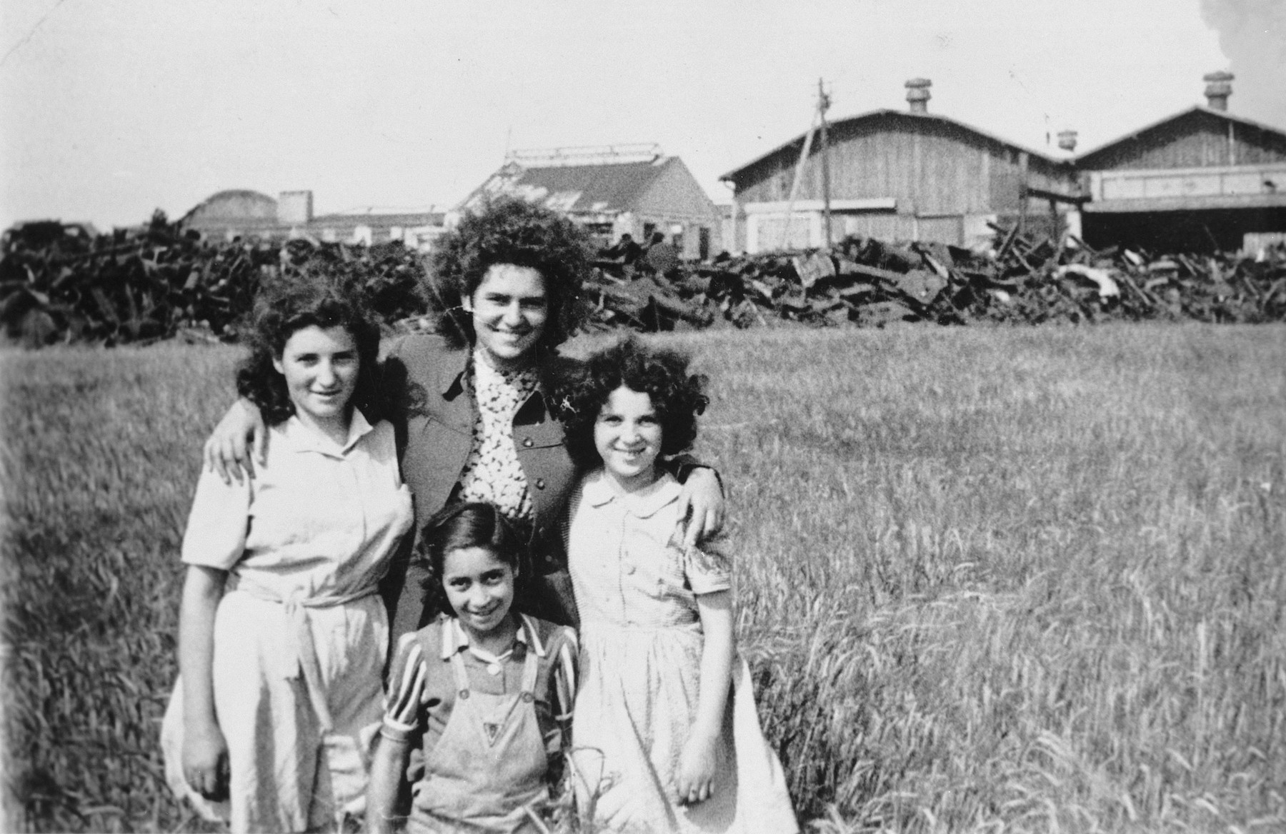 A female counselor poses with three girls in the Rosenheim displaced persons' camp.  Pictured in the back is Fira (Esther) Scapinker.
