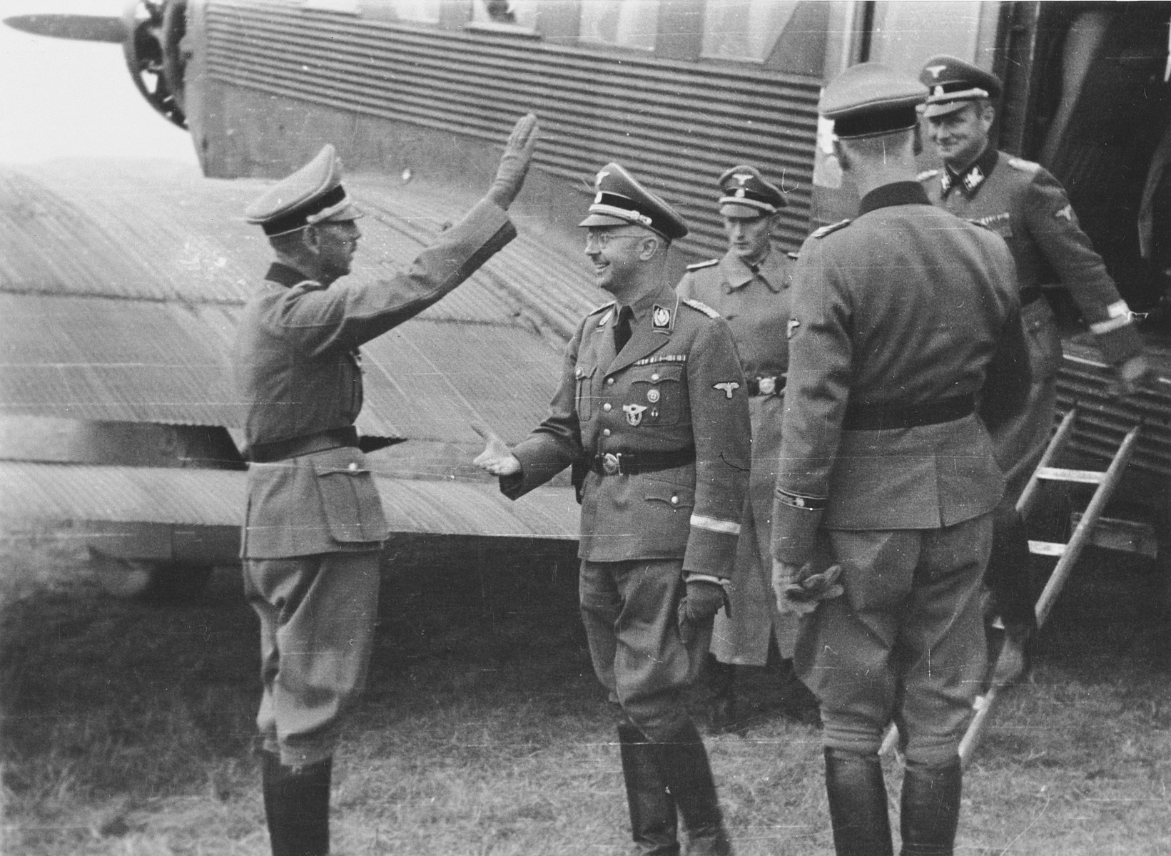 "Heinrich Himmler arrives at the airport on a visit to the volunteer Prinz Eugen division. Karl Wolff can be seen stepping off the plane.   The original Waffen-SS caption reads ""Der Reichsfuehrer SS Heinrich Himmler bei der Ankunft auf einem Feldflughafen zur Besichtigung der SS Freiwilligen-Division"" (The Reichsfueher SS Heinrich Himmler arrives at the field airport on his visit to the SS volunteer division)."